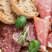assorted Italian antipasti - deli meats, olives and bread, close-up, top view